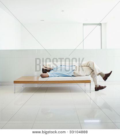 Senior African man laying on bench