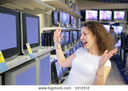 Young Woman In Delight Looks At Tvs In Shop