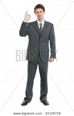 Full Length Portrait Of Businessman Showing Ok Gesture