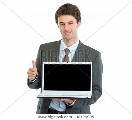 Modern Businessman Showing Laptops Blank Screen And Thumbs Up