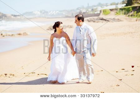 feliz novio y novia caminando en la playa