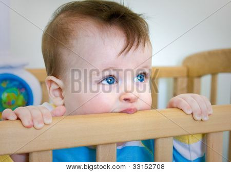 Baby Boy chomps his wooden bed