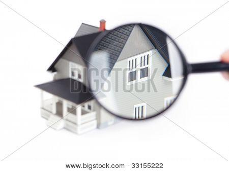 Conceito imóveis - mão segurando a lupa na frente o modelo arquitetônico da casa, isola