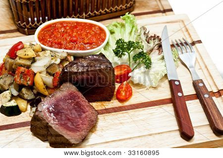 Rare steak with grilled vegetables on wooden plate