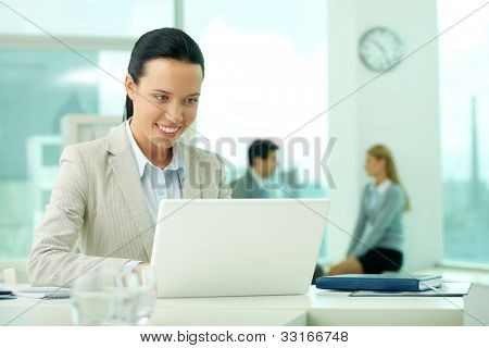 Portrait of pretty secretary looking at laptop screen while typing