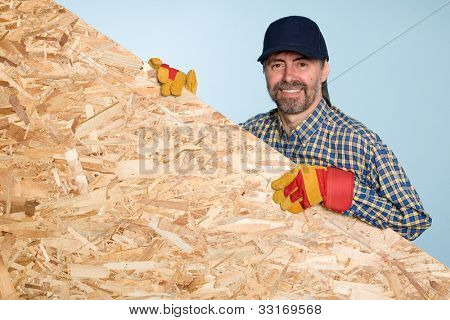Cheerful carpenter holds a sheet of plywood.