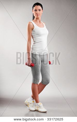 sporty woman is standing with barbells on grey background