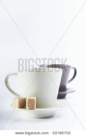 two cups with brown sugarcubes on white background