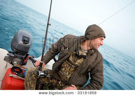Fisherman fishing a salmon trolling in the sea.