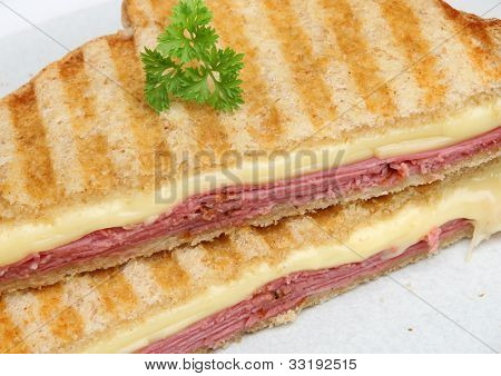 Toasted sandwich with beef pastrami and melting cheese.