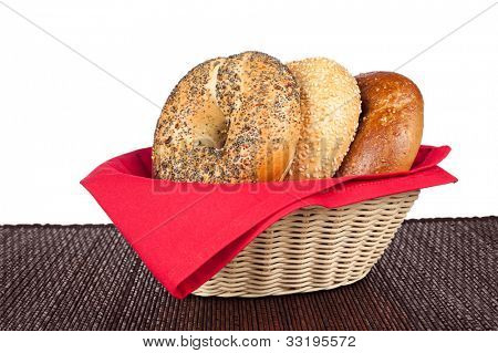 A wicker basket with three bagels including an onion bagel, sesame seed bagel and a wholegrain wheat bagel against a white background