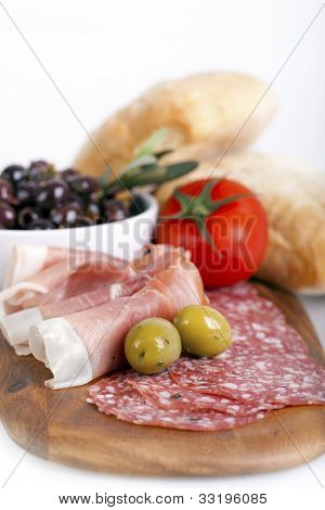 A platter of cold meats, olives, tomato and bread rolls. Tapas style assortment. Intentional shallow depth of field.