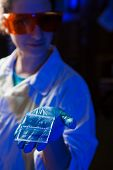 foto of electrophoresis gel  - Female researcher in protective glasses holding in hand an agarose gel plate with results of DNA analysis - JPG