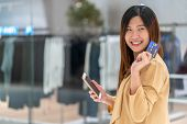 Portrait Asian Woman Using Credit Card With Smart Mobile Phone For Online Shopping In Department Sto poster