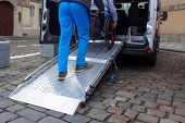 Assistant Helping Disabled Person On Wheelchair With Transport Using Accessible Van Ramp poster