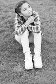 Cute Daydreamer. Girl Little Kid Spend Leisure Outdoors In Park. Girl Sit On Grass In Park. Child En poster