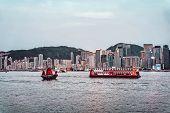Junk Boat At Victoria Harbor Of Hong Kong At Sundown poster
