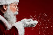 Side View Portrait Of Classic Santa Claus Blowing Snow While Standing Against Red Background, Copy S poster
