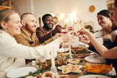 Multi-ethnic Group Of People Raising Glasses Sitting At Beautiful Dinner Table Celebrating Christmas poster