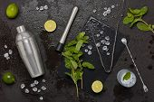 Set of bar tools: cocktail shaker, muddler, bar spoon, ice tongs and glass with ice, lime and mint   poster
