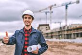 Civil Engineer In A White Helmet On The Background Of Construction, With A Raised Thumb. poster