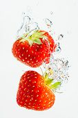 Strawberry Falls Deeply Under Water With A Big Splash. Fruit Sinking In Clear Water On White Backgro poster