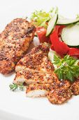 Spicy grilled chicken white meat with salad and herbs poster