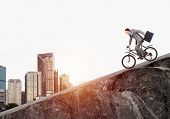 Young Man On Bicycle Fast Riding Downhill At Sunny Day. Businessman On Bike Hurry To Work. Corporate poster