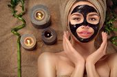 Beautiful woman with black purifying black charcoal mask on her face. Beauty model girl with black f poster