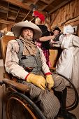 foto of antique wheelchair  - Injured mature cowboy in wheelchair at old west saloon - JPG