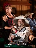 image of sneaky  - Sneaky old poker player gets winning card from showgirl in saloon - JPG