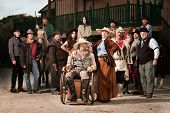 stock photo of antique wheelchair  - Old west theme Senior couple with group of people - JPG
