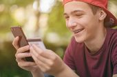 Happy young man is using smartphone and bank card for online shopping.  Teenage boy with a credit ca poster