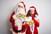 Couple wearing Santa costume holding wow and sale banner over isolated white background afraid and s poster