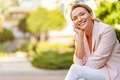 Close-up portrait of a smiling woman on the street. Happy womans face closeup, outdoors. Happy busi poster