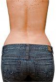stock photo of derriere  - Young woman showing her smooth skinned back and derriere wearing blue jeans isolated on white - JPG
