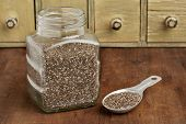 pic of tablespoon  - chia seeds in glass jar and on measuring aluminum tablespoon with a vintage drawer cabinet in background - JPG