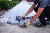 The master in yellow gloves lays paving stones in layers. Garden brick pathway paving by professiona poster