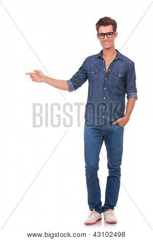 casual young man holds a hand in his pocket and points in a side direction while looking at you and smiling. isolated on a white background