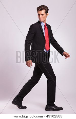full length picture of a young business man walking forward and looking back - side view