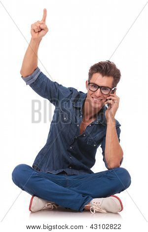 casual young man speaking on the phone and pointing upwards while smiling to the camera, from a cross legged position. isolated on white