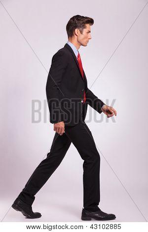 Seite Portrait of a young Business-Man zu Fuß auf grauem Hintergrund und Wegsehen