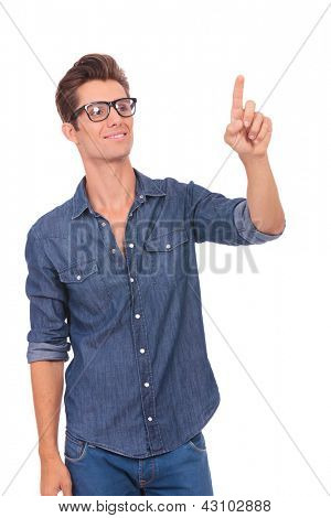 casual young man pushing an imaginary button and looking at it with a smile on his face. isolated on a white background