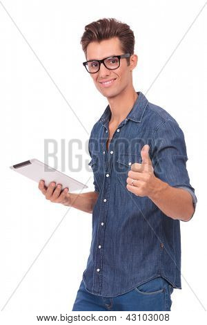 casual young man holding a tablet in one hand and showing thumbs up with the other while smiling at you. isolated on a white background
