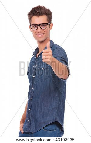 casual young man showing thumbs up to the camera with a hand in his pocket and a smile on his face. isolated on a white background