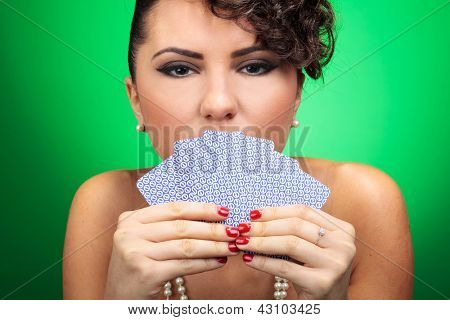 sexy young woman concealing her mouth with her poker hand while looking deep into your eyes. on green background