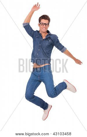casual man jumping and smiling to the camera, over white background