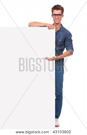 casual young man presenting a big blank board while smiling to the camera. isolated on a white background