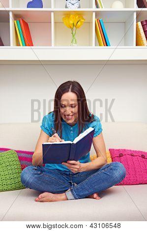 mujer joven sonriente escribiendo en agenda