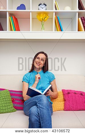 smiley thoughtful woman holding pen and notebook